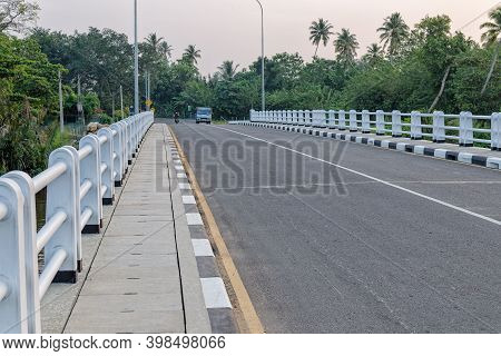 View Of The Asphalt Bridge In The Tropic Country. Pedestrian Walkway Made Of Concrete Slabs On The B