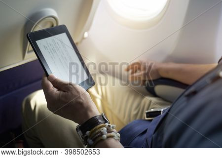 Asian Man Male Passenger Sitting In Cabin Of Airplane Reading Ebook Using E-reader