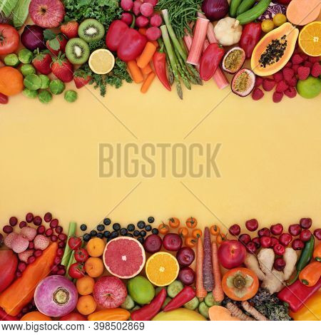 Antioxidant health food to fight free radicals with fruit and vegetable high in fibre, anthocyanins, lycopene, protein, vitamins, minerals and carotenoids. Healthy lifestyle concept. Border on yellow.