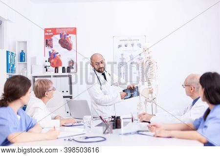 Surgeon Holding Radiography And Making Presentation In Front Of Colleagues In Hospital Meeting Room.