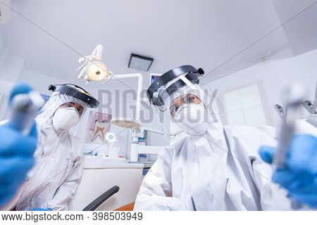 Patient Pov Of Orthodontist And Assistan Doing Procedure For Mouth Hygine In Coverall. Stomatology T