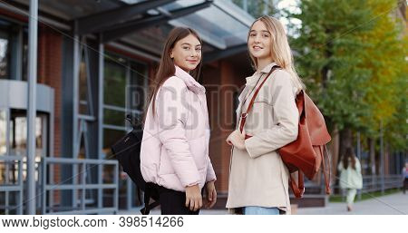Portrait Of Caucasian Happy Pretty Girls Students Talking While Standing Outdoor And Smiling To Came