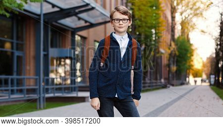 Happy Caucasian Schoolboy Looking Away And Turning Head To Camera. Joyful Male Pupil In Glasses With