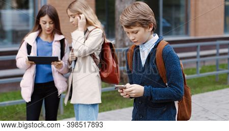 Portrait Of Caucasian School Student Boy Going To School And Typing On Cellphone Outdoors. Male Pupi