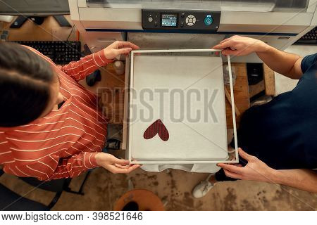 Top View Of Young Workers, Man And Woman Looking At The Result Of Printing T-shirt In The Silk Scree