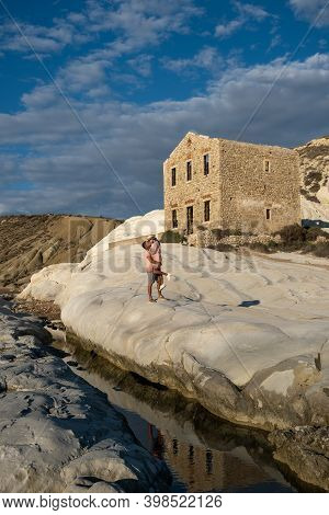 Punta Bianca Sicily, A Couple Watching The Sunset At The White Cliffs With An Abandoned House At Pun