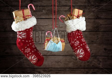 Two Christmas Stockings And A Protective Face Mask Against Covid-19 Infection Filled With Gifts And