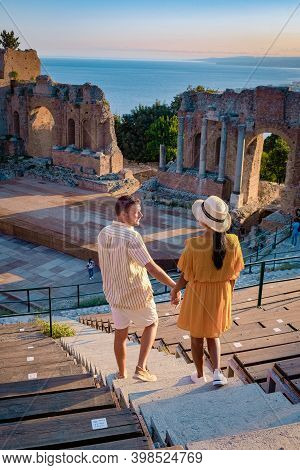 Taormina Sicily, Couple Watching Sunset At The Ruins Of The Ancient Greek Theater In Taormina, Sicil