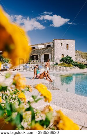 Couple On Luxury Vacation Relaxing By The Pool At An Agriturismo In Sicily Italy. Mid Age Couple On
