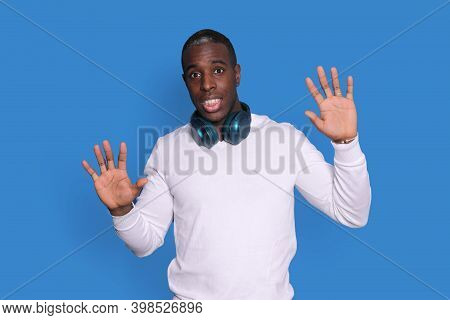 Perplexed Black Man Guy In White Street Wear Sweater Posing Isolated On Blue Background, Rising Hand