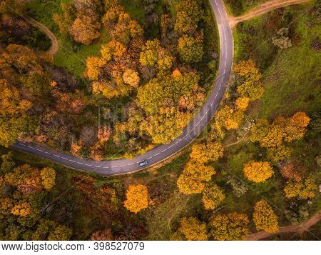 Birds-eye View Of A Black Car Passing Around A Bend Along A Tarmac Road Passing Through A Woodland I