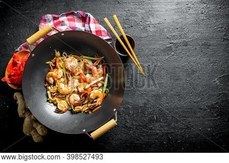 Finished Udon Noodles In A Wok Pan With Soy Sauce, Chopsticks And A Napkin. On Black Rustic Backgrou