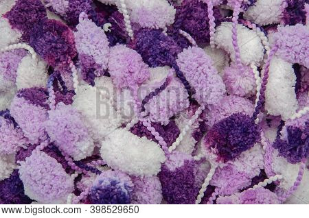Hanks Of White, Violet And Purple Pompons. Knitter Background. Top View.