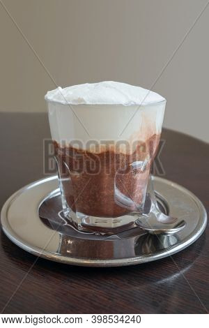 Traditional sicilian Granita cold sweet dessert with chocolate flavor and fresh cream close-up on the table in cafe