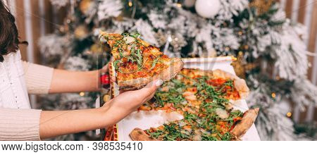Close Up Photo Of Woman Hand Holding Slice Of Fresh Pizza Over Christmas Tree Background