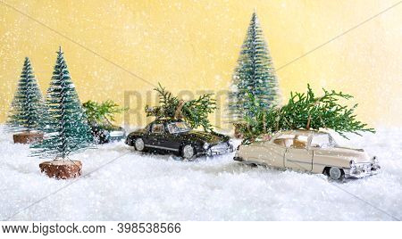 Toy Cars In The Forest Among The Snowdrifts, Deliver Christmas Trees. Blurred Background. Magic Atmo