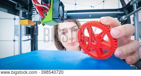 Young women designer in 3d printing lab. Girl takes the finished detail from 3D printer