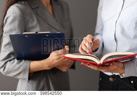 Two Businesswomen Communicate At Work In Office. Delegation Of Authority Concept
