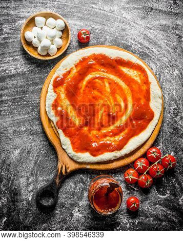 Raw Pizza. Rolled Out Dough With Tomato Paste, Mozzarella And Fresh Tomatoes. On Rustic Background