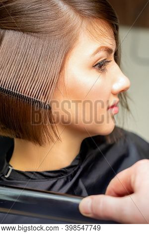 Closeup Of A Hairdresser Straightening Short Brown Hair With Hair Iron In A Hair Salon