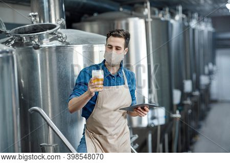 Product Quality And Beer Production In Brewery. Millennial Worker In Apron And Protective Mask Holds