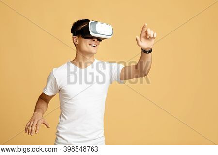 Man Have Fun With Virtual Reality Headset. Cheerful Young Guy Student In White T-shirt And Virtual R