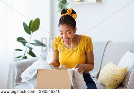Satisfied Buyer. Portrait Of Curious Cheerful Black Woman Received Package, Unpacking Cardboard Box,