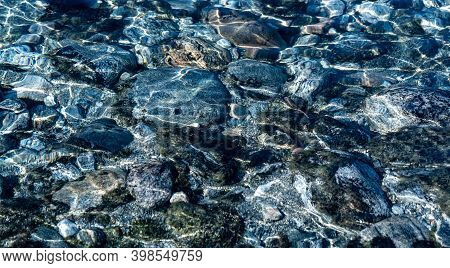 Crystal Clear Glacial Melting Water Running Over Smooth Rocks And Pebbles In A Wild Forest River. Cl