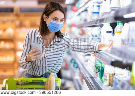 Young Woman In Disposable Face Mask Taking Dairy Products From Shelf In The Supermarket, Holding Sma