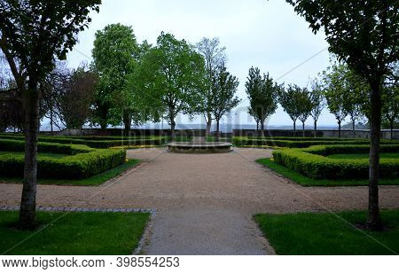 Buxus sempervirens ornamental boxwood hedge trimmed and beige threshing paths in the park round bowl or pond rainy lawns symmetrical composition