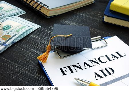 Graduation Cap And Financial Aid For Student Form On The Desk.