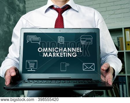 Cross-channel Or Omnichannel Marketing. The Manager Demonstrates A Laptop With A Report.