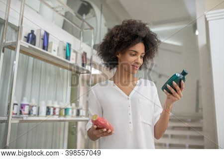 Joyful Girl Holding And Looking At Bottles Of Cosmetics