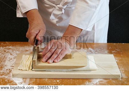how to make japanese udon noodles; cut the rolled out dough with a knife.