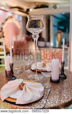 The Table Is Serviced For Two People Newlyweds. Stands Decorated Cutlery, Candles In The Banquet Hal