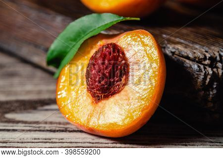 Peach With Leaf On Wooden Table. Peach In Half. Ripe Juicy Peaches. Harvest Of Peaches For Food Or J