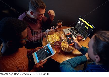Gadgets. Excited Fans In Bar With Beer And Mobile App For Betting, Score On Their Devices. Screen Wi