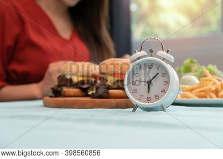 Selective Focus Of Clock, Young Woman Ready To Eating A Hamburger, French Fries, For Breakfast. Conc