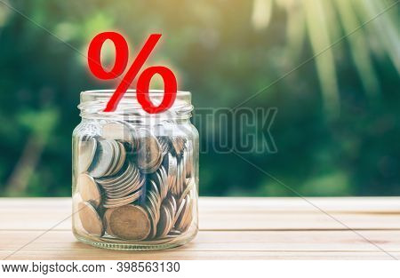 Money Jar And Interest Illustrations Placed On The Table. Concept Of Saving Money To Pay Interest Or