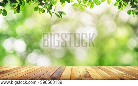 Empty Brown Wooden Table With Fresh And Green Leaves Green Bokeh On Nature Abstract Blur Background