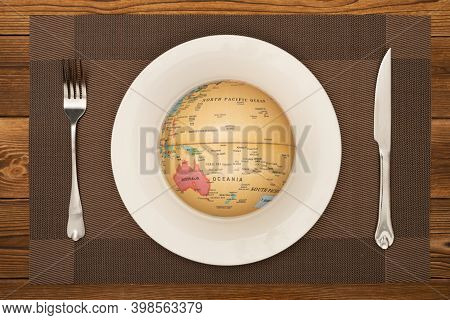 Globe On A Dish With Fork And Knife Nearby Concept Of Overusing The Resource Of Nature