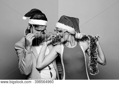 Happy Man And Woman Wear Santa Hats And Funny Sunglasses. Cheerful Couple Celebrate New Year. Corpor