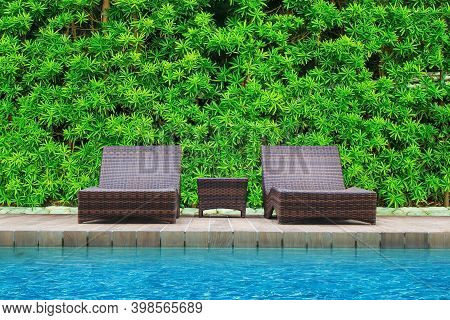 Wooden Daybed Place On Wooden Floor Beside Swimming Pool In The Resort With Green Bush In Background