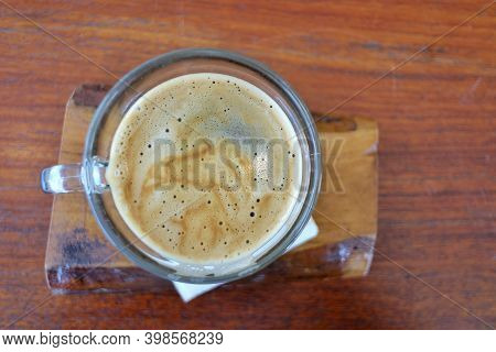 A Cup Of Hot  Coffee On Wooden Dinning Table Top View