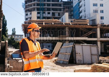 Construction Supervisor Using Laptop At Construction Site On Sunny Day