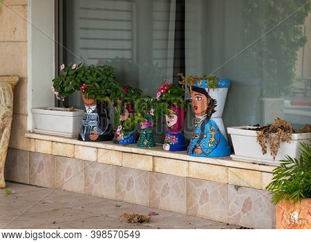 Nazareth, Israel, December 05, 2020 : Flower Pots Painted Like Dolls In National Clothes In The Musl
