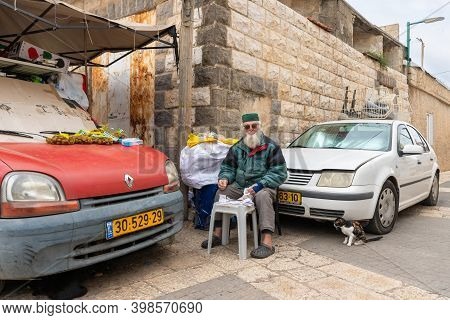 Nazareth, Israel, December 05, 2020 : Elderly Muslim Sits Outside His House And Deals With Receipts