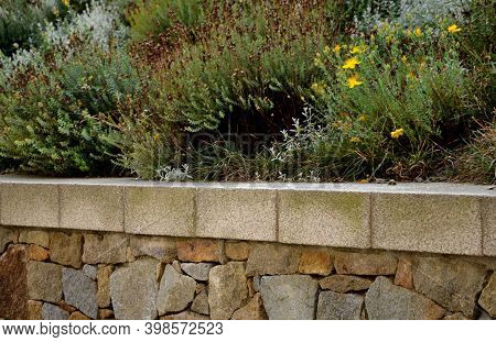 Beautifully Folded Retaining Wall With A Granite Attic With Small Joints. Brown Beige Yellow Irregul