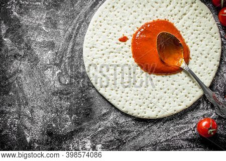 Raw Pizza. Pizza Dough With Tomato Paste. On Rustic Background