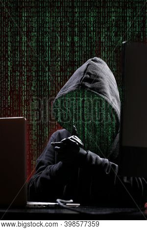 International Hacker In Black Pullover And Black Mask Trying To Hack Government On A Black And Red B
